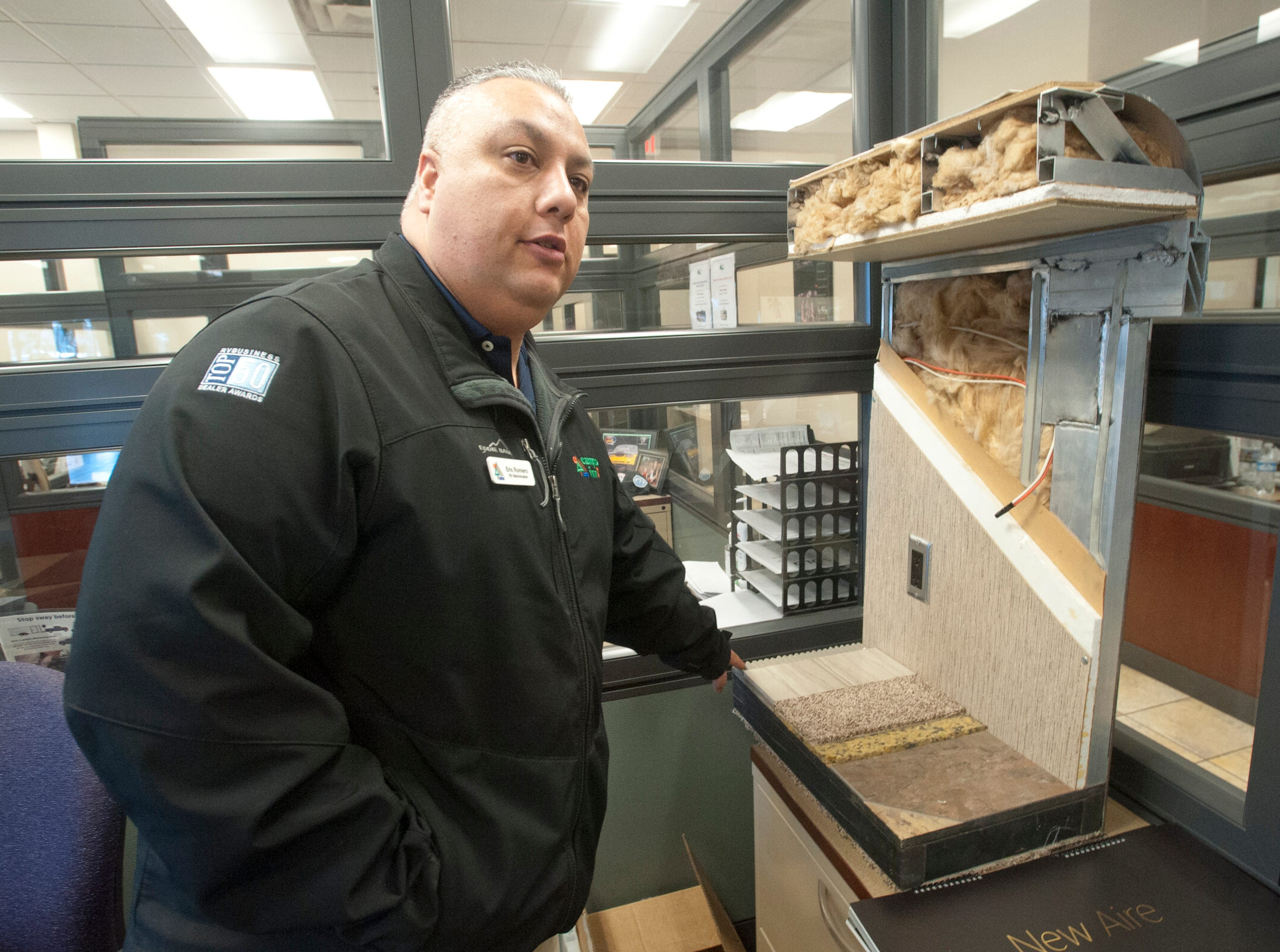 Eric Romero, sales representative for Campers Inn in Clarksville, shows a model of the under skin of the recreational vehicle including heated flooring options and the fiberglass that is used to insulate the vehicle.11 December 2018