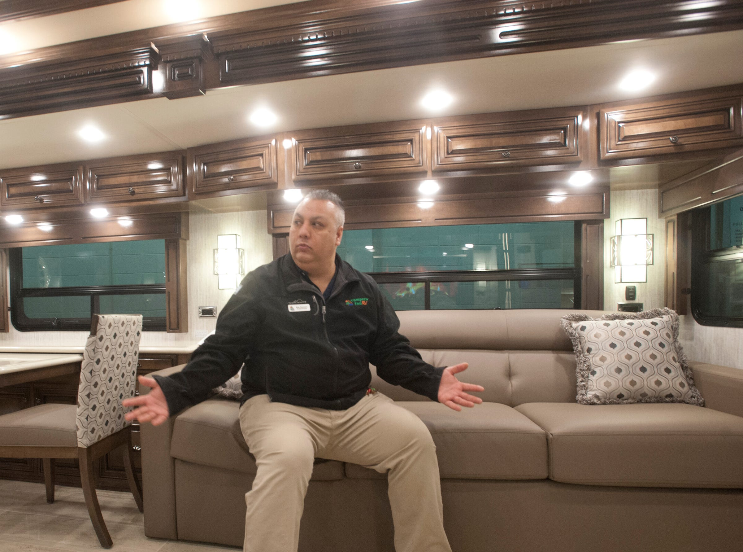 Eric Romero, sales representative for Campers Inn in Clarksville, sits atop the driver's side living room couch of the Dutch Star as he explains the recreational vehicle's features. The couch contains a fold-out bed.11 December 2018