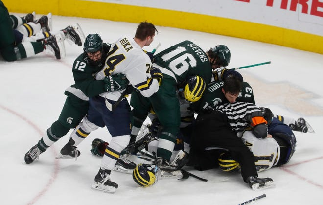 Officials separate members of Michigan and Michigan State during the first period of a Great Lakes Invitational college hockey game, Monday, Dec. 31, 2018, in Detroit.