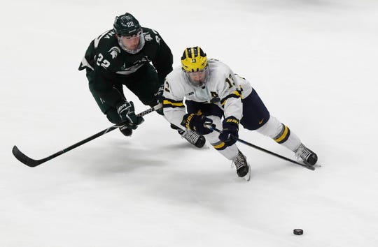 Michigan forward Jake Slaker (13) and Michigan State defenseman Dennis Cesana (22) chase the puck during the third period of a Great Lakes Invitational college hockey game, Monday, Dec. 31, 2018, in Detroit.