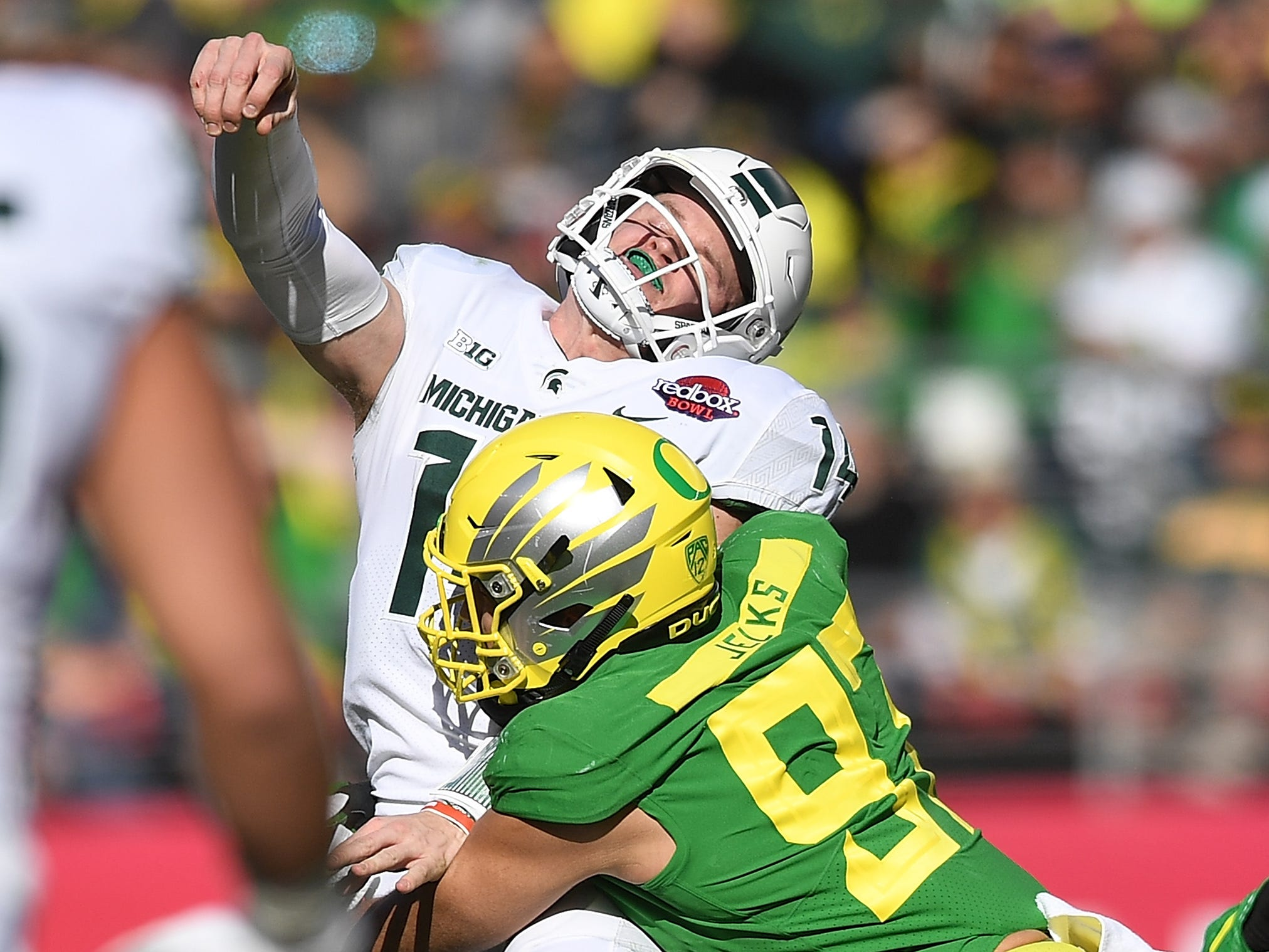 Brian Lewerke #14 of the Michigan State Spartans gets his pass off under pressure from Jalen Jelks #97 of the Oregon Ducks during the first half of the Redbox Bowl at Levi's Stadium on December 31, 2018 in Santa Clara, California.