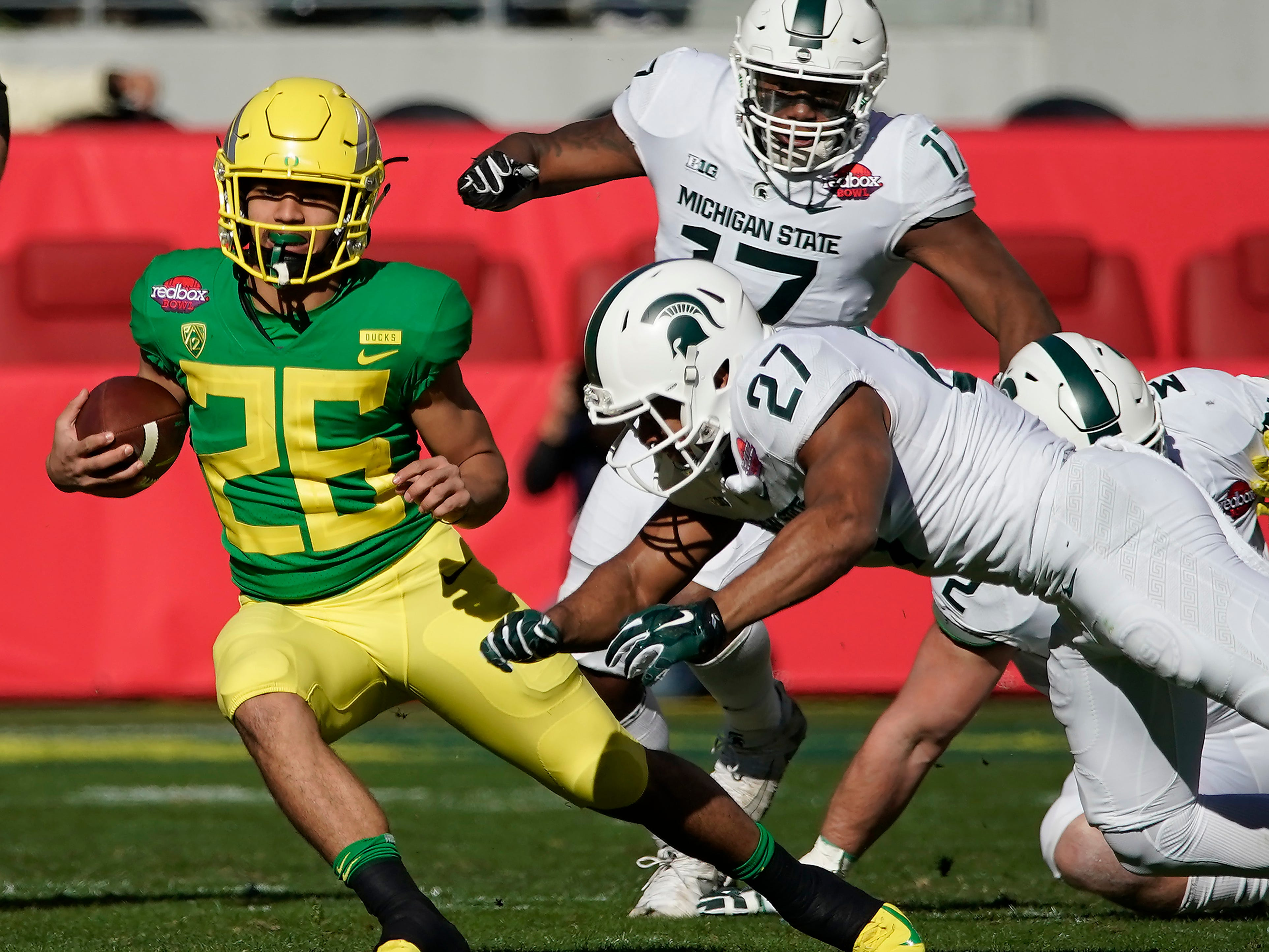 Oregon Ducks running back Travis Dye (26) rushes for a first down past Michigan State Spartans safety Khari Willis (27) during the first half of the Redbox Bowl NCAA college football game Monday, Dec. 31, 2018, in Santa Clara, Calif.