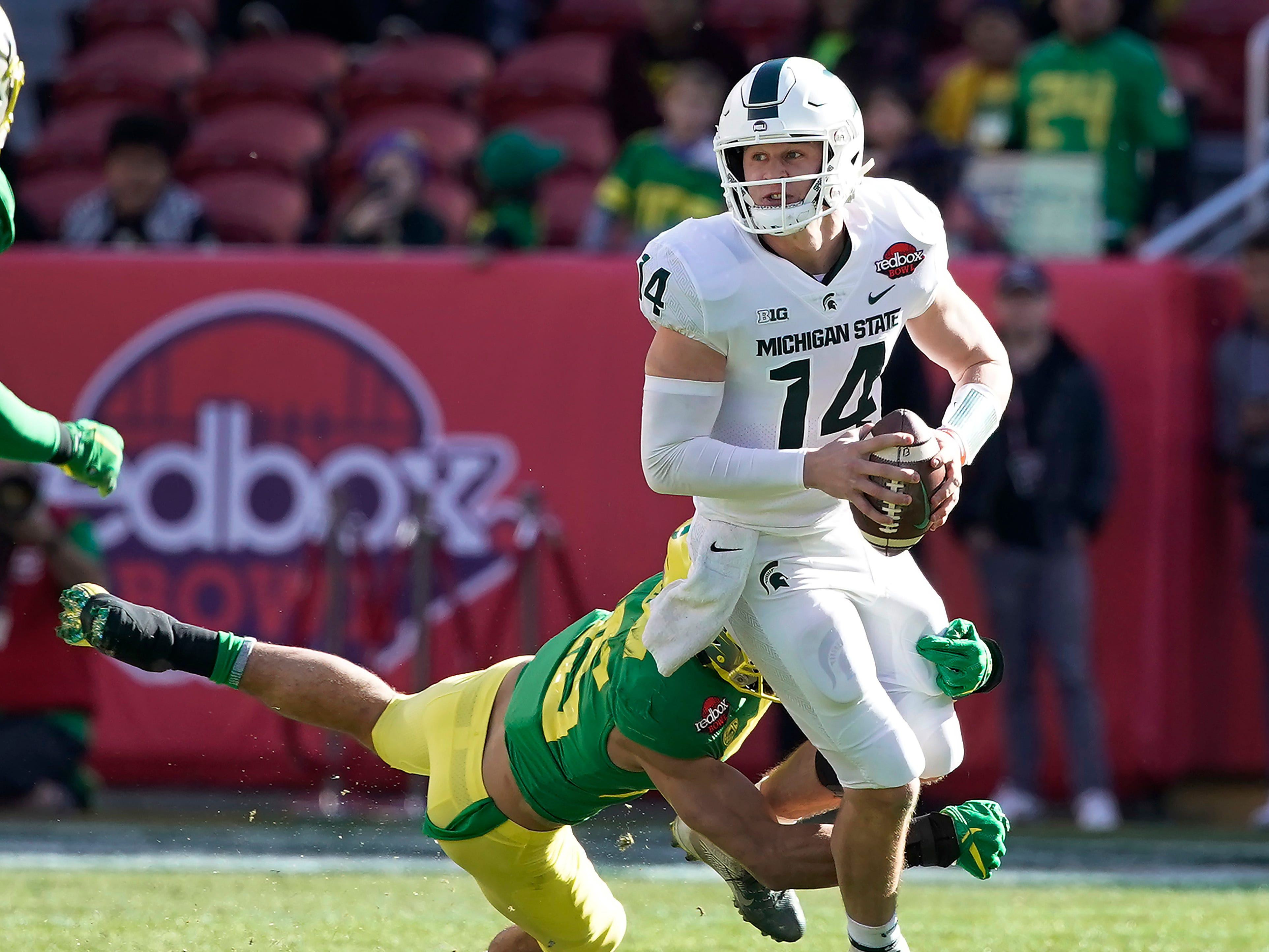 Michigan State quarterback Brian Lewerke (14) is sacked by Oregon safety Brady Breeze (25) during the first half of the Redbox Bowl NCAA college football game Monday, Dec. 31, 2018, in Santa Clara, Calif.