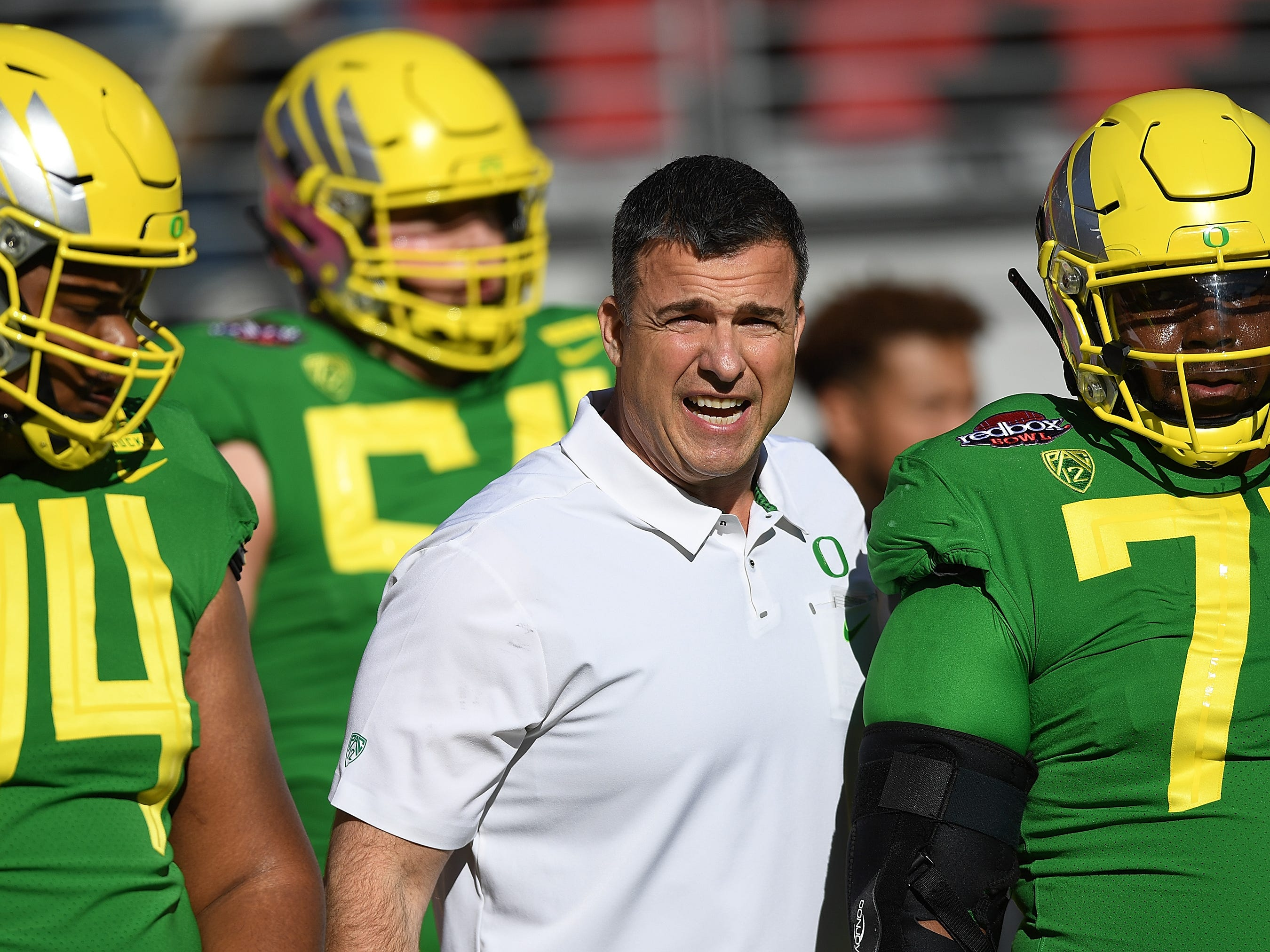 Head coach Mario Cristobal of the Oregon Ducks works with his players during pre-game warm ups prior to the start of the Redbox Bowl against the Michigan State Spartans at Levi's Stadium on December 31, 2018 in Santa Clara, California.