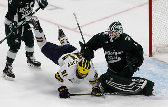 Michigan forward Nick Pastujov (91) falls in front of Michigan State goaltender Drew DeRidder (1) during the second period of a Great Lakes Invitational college hockey game, Monday, Dec. 31, 2018, in Detroit.