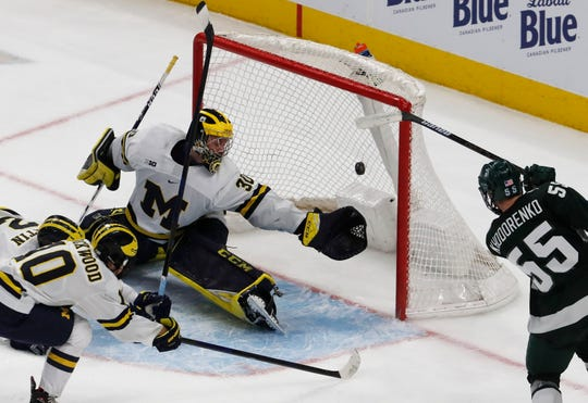 Michigan State forward Patrick Khodorenko (55) scores on Michigan goaltender Hayden Lavigne (30) during the first period of a Great Lakes Invitational college hockey game, Monday, Dec. 31, 2018, in Detroit.