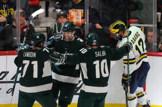 Michigan State forward Wojciech Stachowiak (18) is congratulated by teammates after scoring during the first period of a Great Lakes Invitational college hockey game, Monday, Dec. 31, 2018, in Detroit.