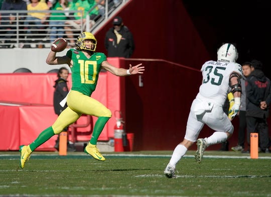 Oregon quarterback Justin Herbert (10) scrabbles for a first down against Michigan State linebacker Joe Bachie (35) during the first half of the Redbox Bowl NCAA college football game Monday, Dec. 31, 2018, in Santa Clara, Calif.