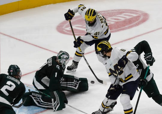 Michigan forward Nick Pastujov (91) scores on Michigan State goaltender Drew DeRidder (1) to tie the score during the third period of a Great Lakes Invitational college hockey game, Monday, Dec. 31, 2018, in Detroit. The game ended in a tie.