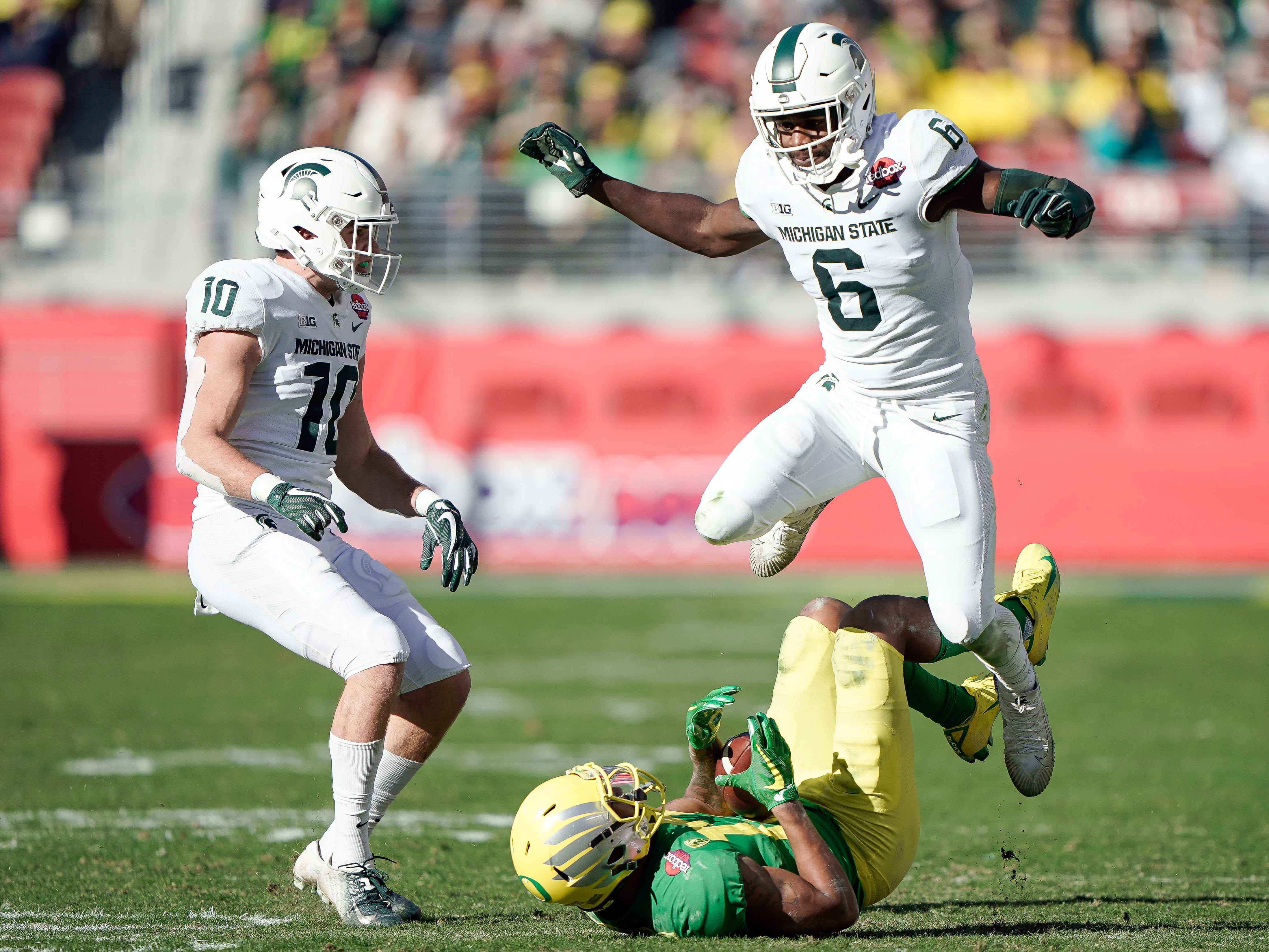 Michigan State Spartans safety David Dowell (6) leaps over Oregon Ducks wide receiver Dillon Mitchell (13) near safety Matt Morrissey (10) during the second quarter at Levi's Stadium.