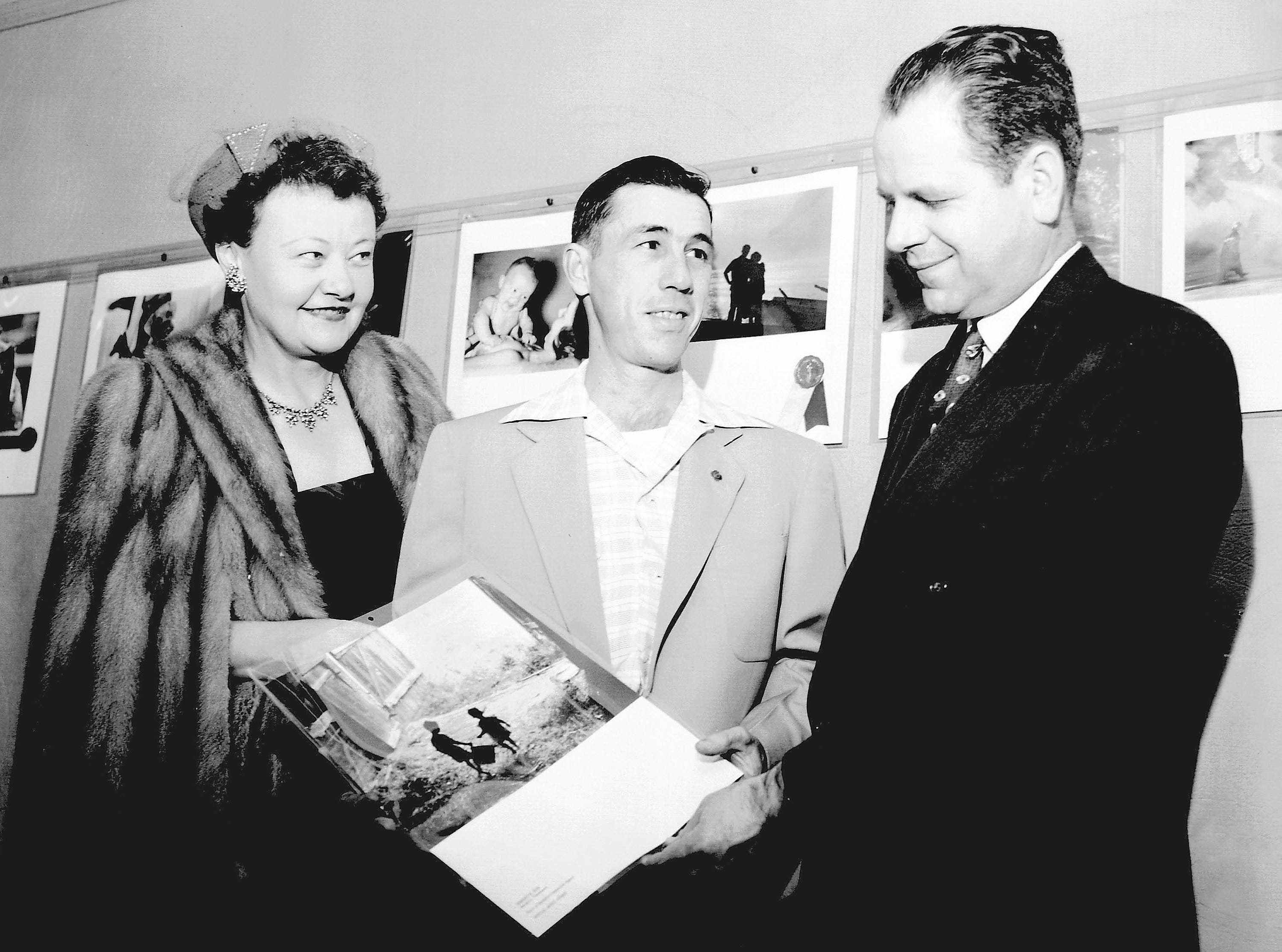 Three grand prize winners in The Commercial Appeal Amateur Snapshot Contest get an advance look at the traveling exhibit of 80 national winners which was on exhibit at Brooks Memorial Art Gallery in January, 1954. Robert Dye (center) shows Miss Eugenia Buxton and John Vookles his $50 Class A national winner, which was included in the exhibit.