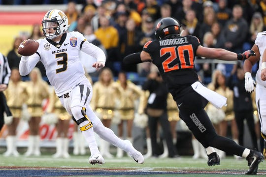 Missouri Tigers quarterback Drew Lock tries to escape the pockt as Oklahoma State Cowboys saftey Malcolm Rodriguez persues during the first half of the Autozone Liberty Bowl in Memphis, Tenn. on Monday, Dec. 31, 2018.