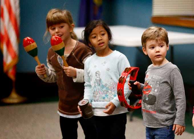 "Children listen to direction from Duke Otherwise to back him up for the song ""What Kind of Hairdo Do You Do?"" during a family performance at the Brookfield Public Library on Dec. 27."