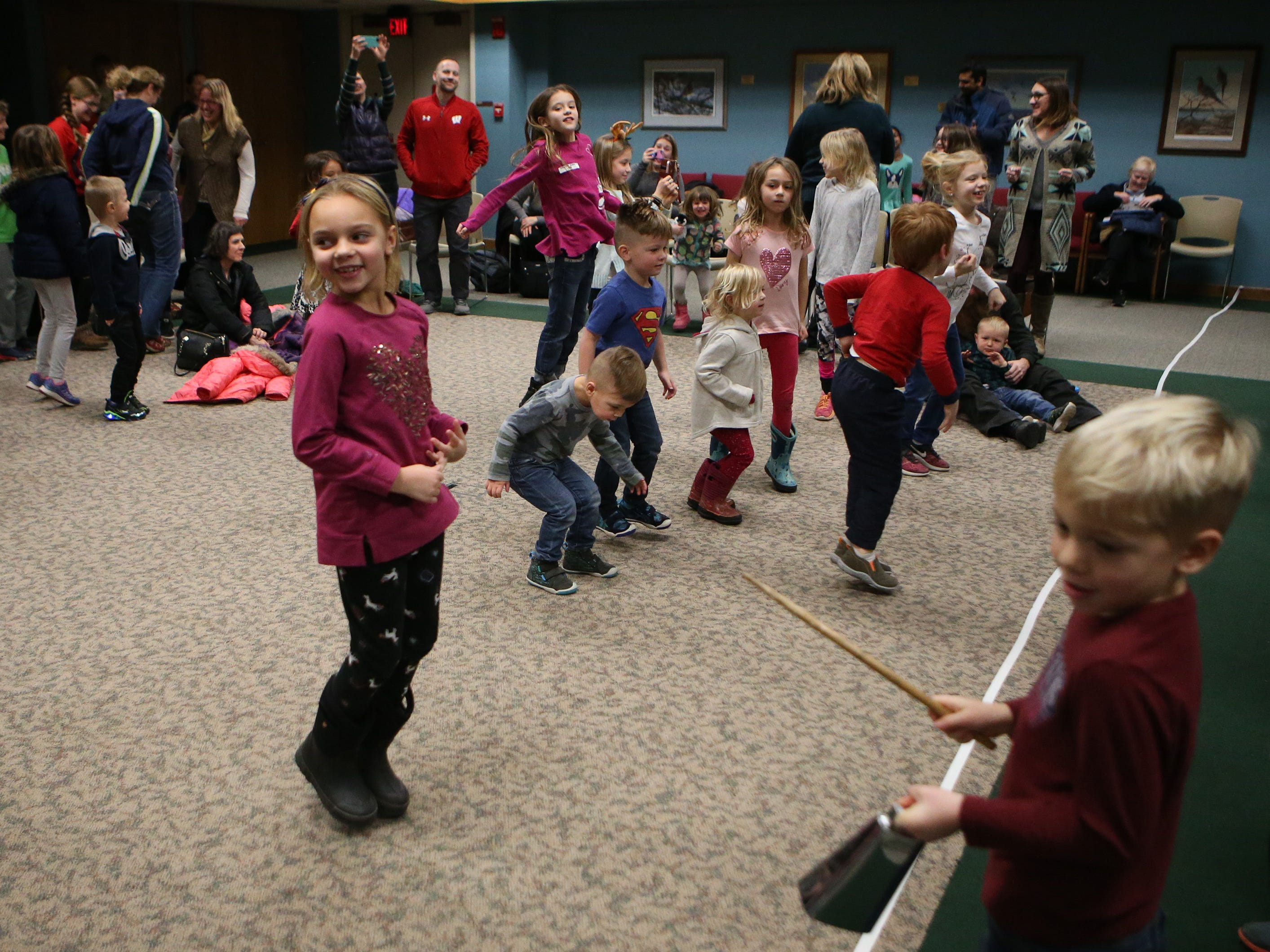 "Children dance along with Duke Otherwise to the song ""What Kind of Hairdo Do You Do?"" during a family performance at the Brookfield Public Library on Dec. 27."