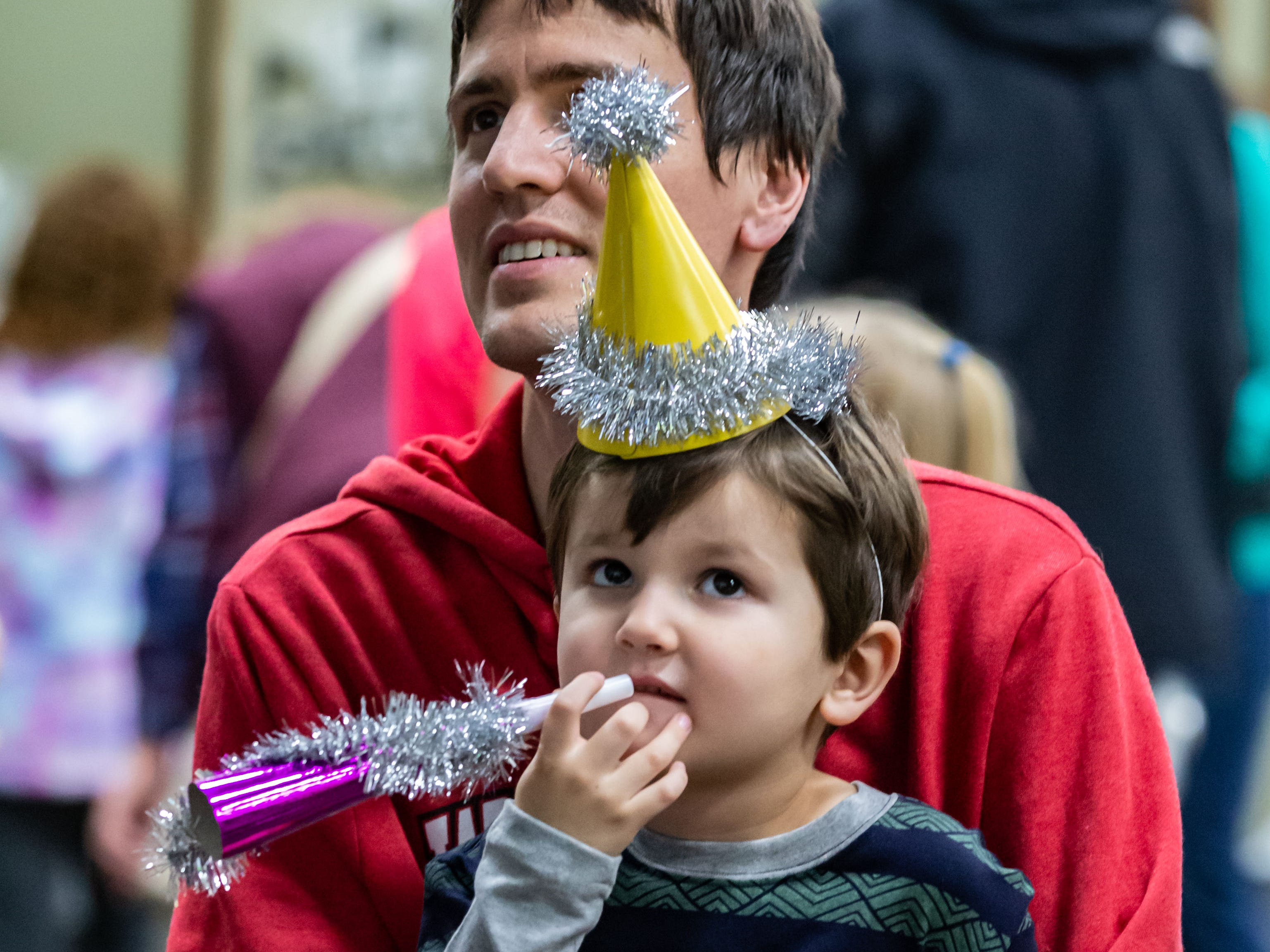 """Brandon Schultz of Mukwonago enjoys a music video with his son Owen, 4, during the """"Noon Year's Eve"""" party at the Mukwonago Community Library on Friday, Dec. 28, 2018. The family friendly event featured crafts, music, dancing and a balloon drop at noon."""