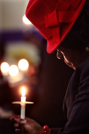 Geneva Fuller holds a candle while the names of the 2018 homicide victims are read Sunday at Crossing Jordan Ministries at 606 W. Concordia Street, Milwaukee. A total of 114 names were listed in the ceremonial program of lives lost to violence. The main themes from the memorial were exercising love while bringing change to Milwaukee