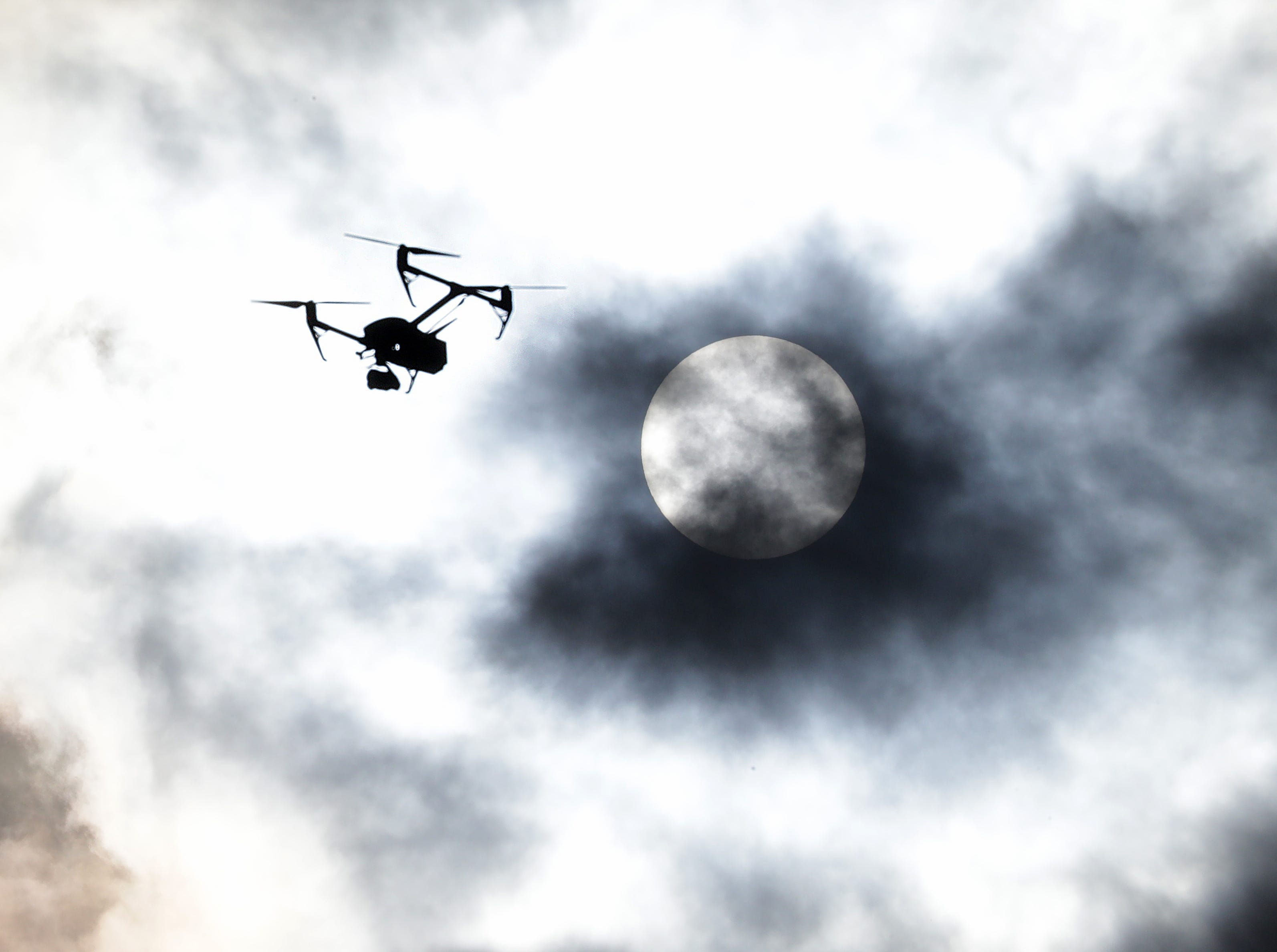 A drone from MKEdrones flies near the Hoan Bridge as a cloud passes over the sun.