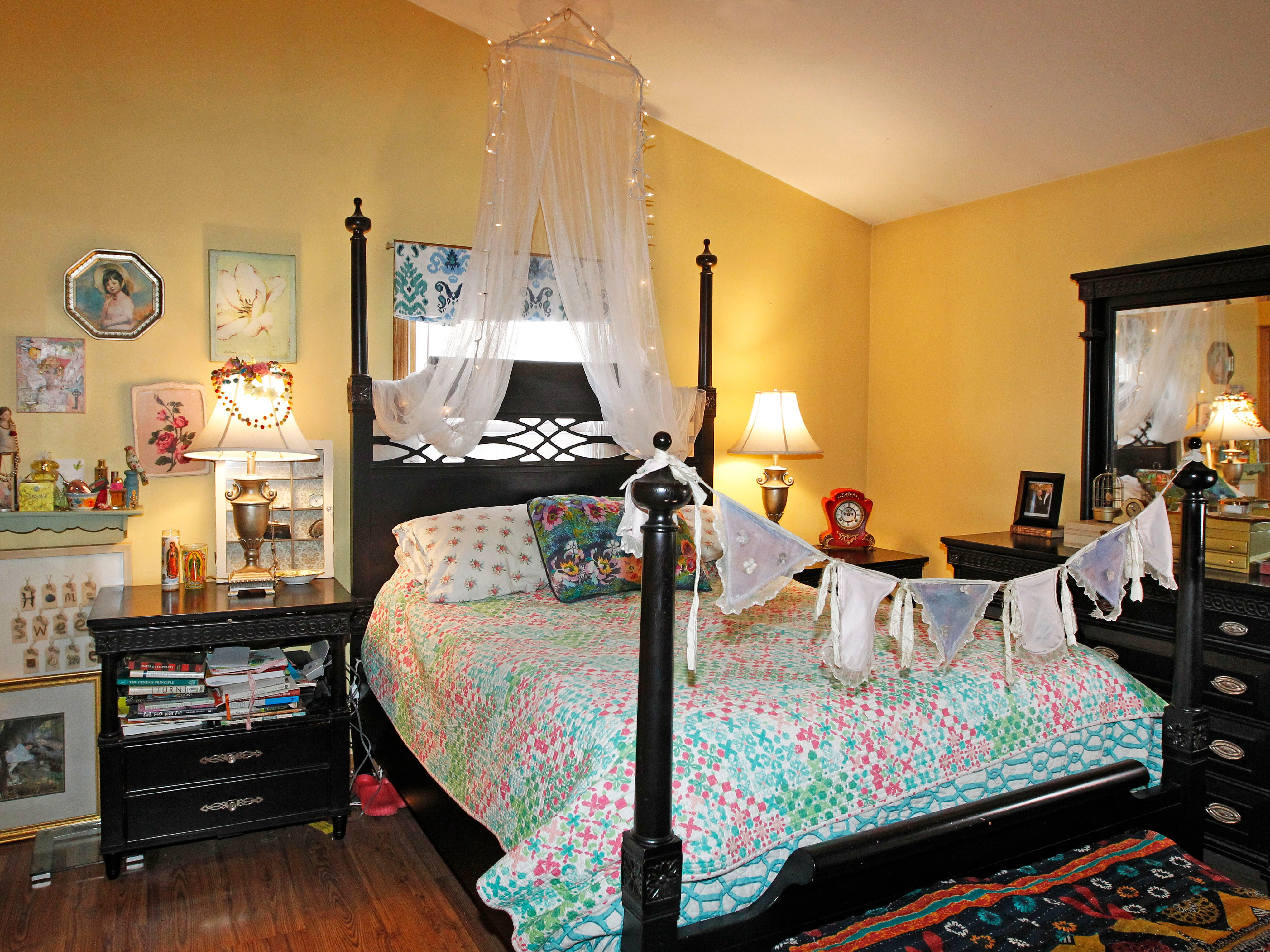 The master bedroom on the home's second floor is decorated with brightly colored artwork.