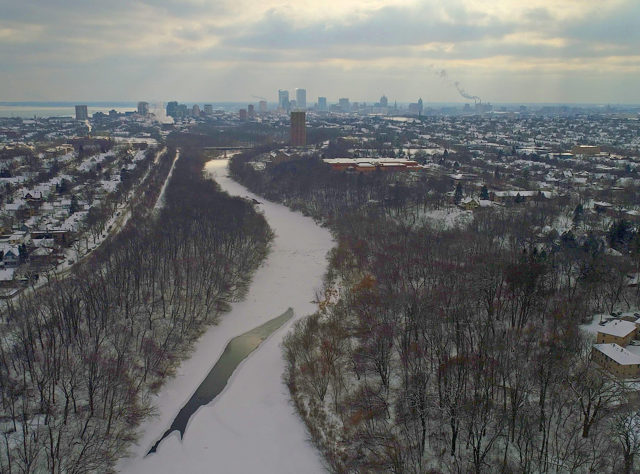 An iced-over Milwaukee River leads south from Shorewood as the Milwaukee skyline is seen in the background.
