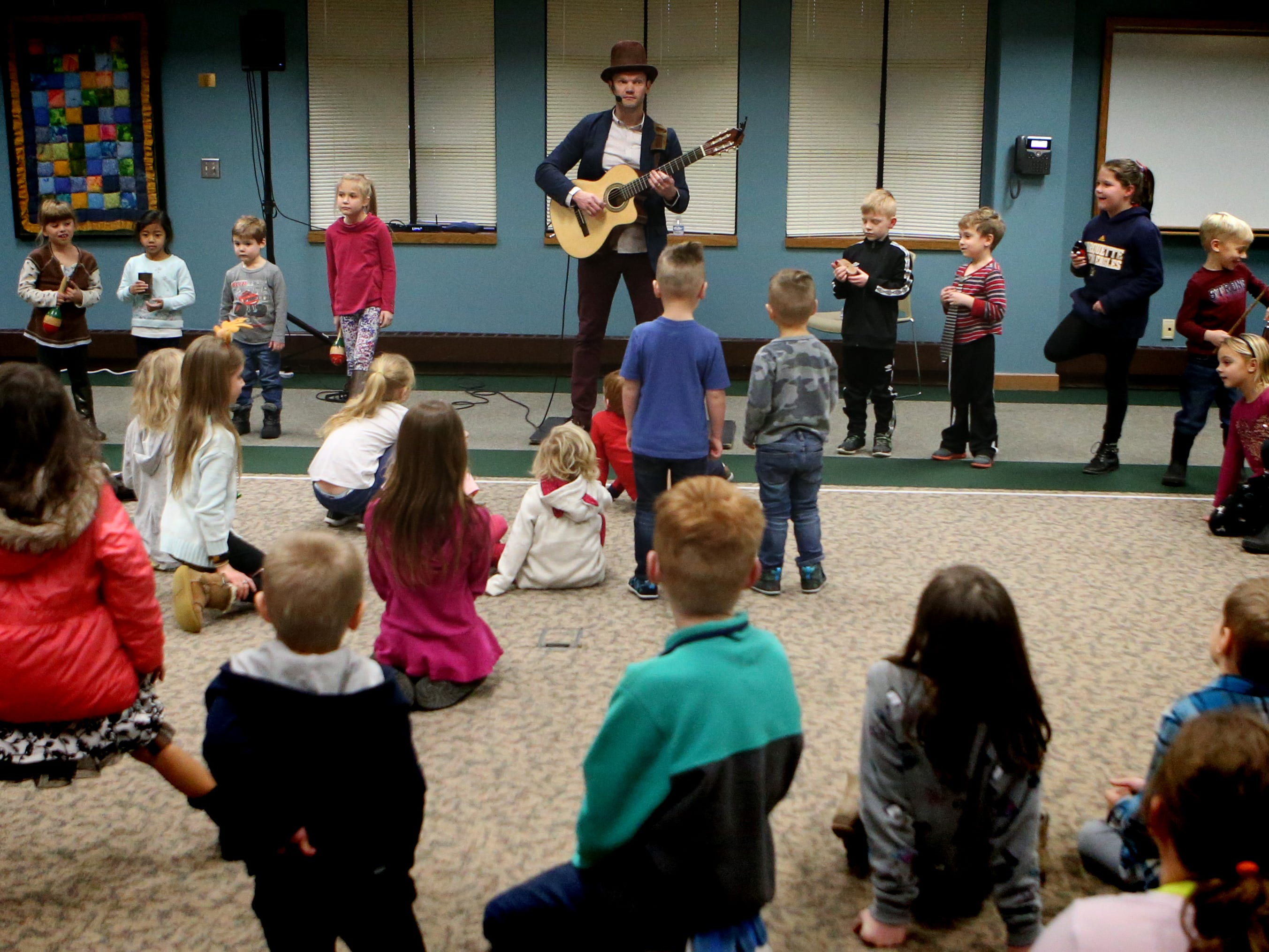 "Duke Otherwise recruits a band to back him up for the song ""What Kind of Hairdo Do You Do?"" during a family performance at the Brookfield Public Library on Dec. 27."