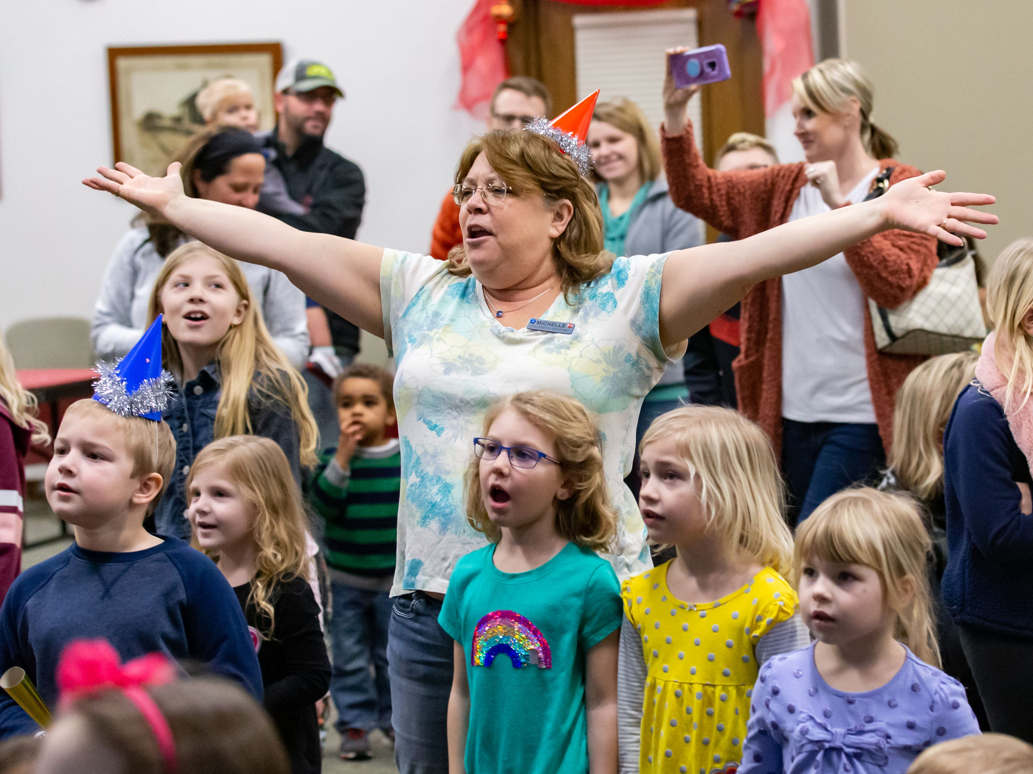 """Youth Services Assistant Michelle Michalik leads youngsters through a Disney song during the """"Noon Year's Eve"""" party at the Mukwonago Community Library on Friday, Dec. 28, 2018. The family friendly event featured crafts, music, dancing and a balloon drop at noon."""