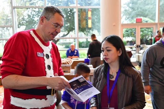 Senior Master Sgt. Eric Vance helps Amanda Untalan during registration for the 10th anniversary Air Force Reserve Yellow Ribbon Reintegration Program event Dec. 14, 2018, in Orlando, Florida. Untalan is a key spouse with the 44th Aerial Port Squadron at Andersen Air Force Base, Guam. Vance is the Yellow Ribbon representative for the 434th Air Refueling Wing at Grissom Air Reserve Base, Indiana.