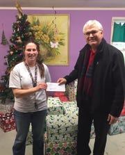 Amanda Cox (left), Jay Retirement Home director, receives a donation from Victor Guerrero, Geneva Red Gold plant manager.