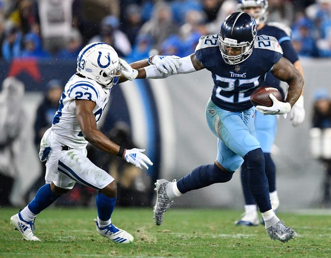 Titans running back Derrick Henry (22) stiff-arms Colts cornerback Kenny Moore II (23) in the third quarter Sunday.