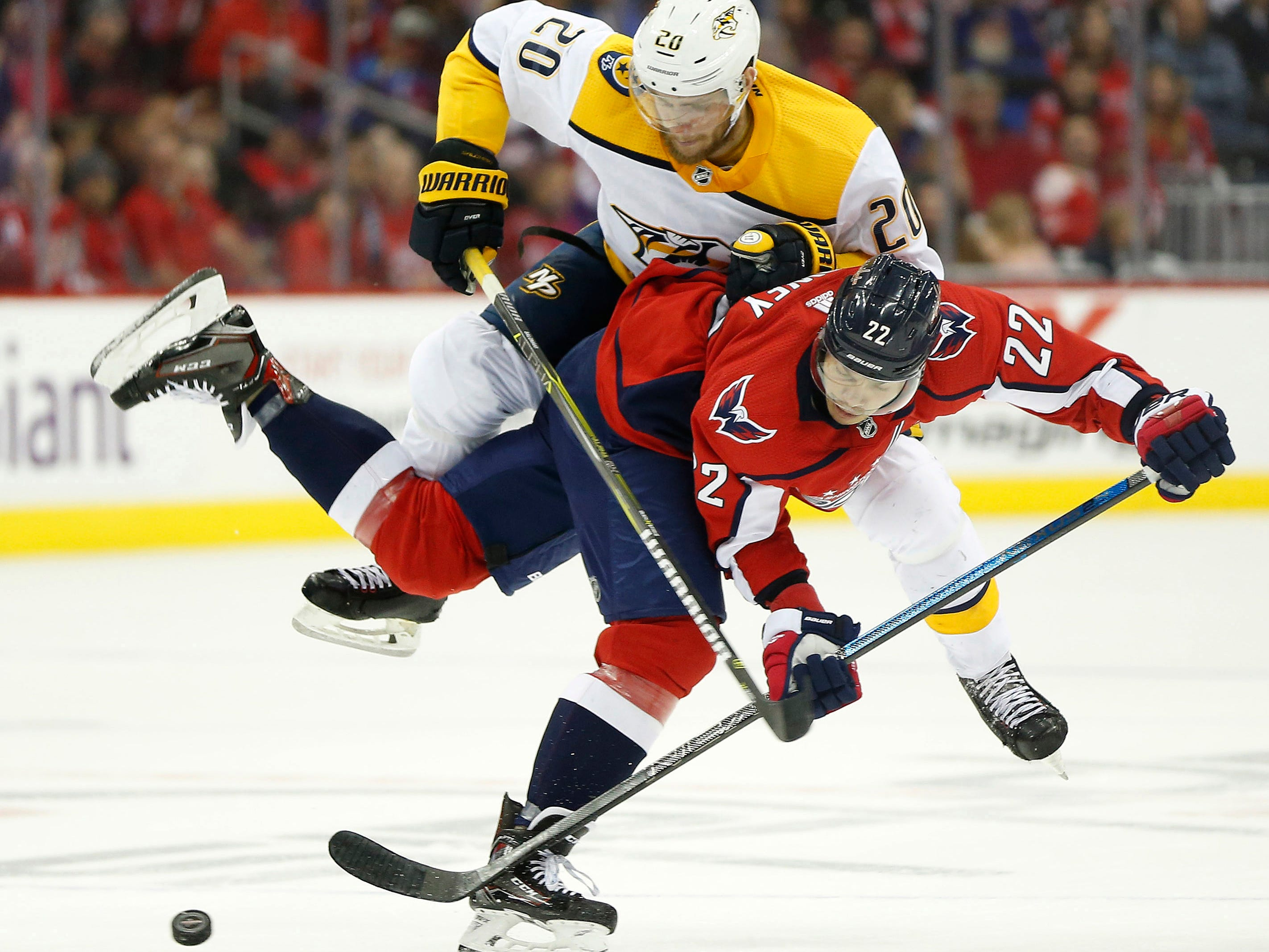 Washington Capitals defenseman Madison Bowey (22) attempts to control the puck as Nashville Predators right wing Miikka Salomaki (20) defends during the second period at Capital One Arena.