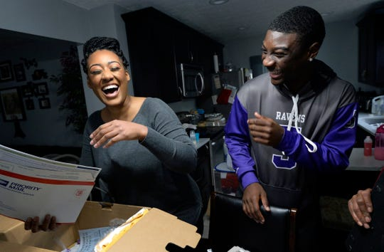Devon Starling and his mother, Tia Starling, laugh as they look through family photographs at their home.