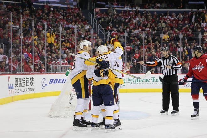 Predators center Rocco Grimaldi (23) celebrates with teammates after scoring a goal against the Capitals during the first period Monday.