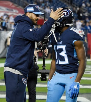 Injured Titans quarterback Marcus Mariota (8) slaps the helmet of wide receiver Taywan Taylor (13) before the game at Nissan Stadium Sunday, Dec. 30, 2018, in Nashville, Tenn.