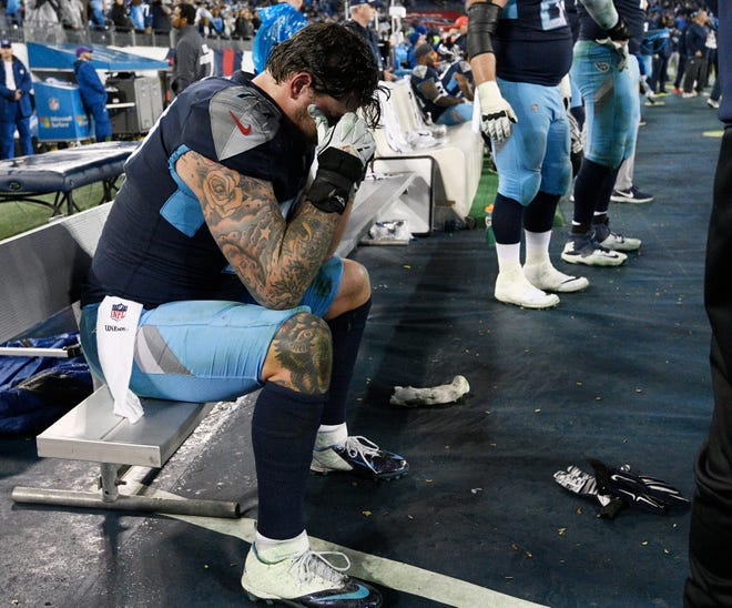 Titans left tackle Taylor Lewan (77) sits on the sideline during the team's 33-17 loss to the Colts on Sunday at Nissan Stadium.