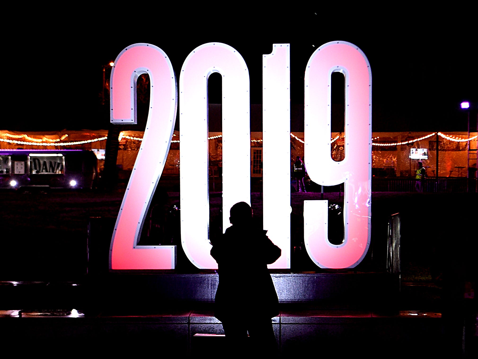 People stop to take photographs of a large 2019 display at Jack Daniel's Music City Midnight: New Year's Eve at Bicentennial Capitol Mall State Park in Nashville on Monday, Dec. 31, 2018.