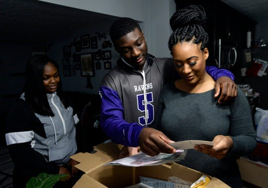 Devon Starling and his mother Tia Starling look at family photographs, Friday, Dec. 21, 2018, in Nashville. His friend Lamia Chancellor looks on.