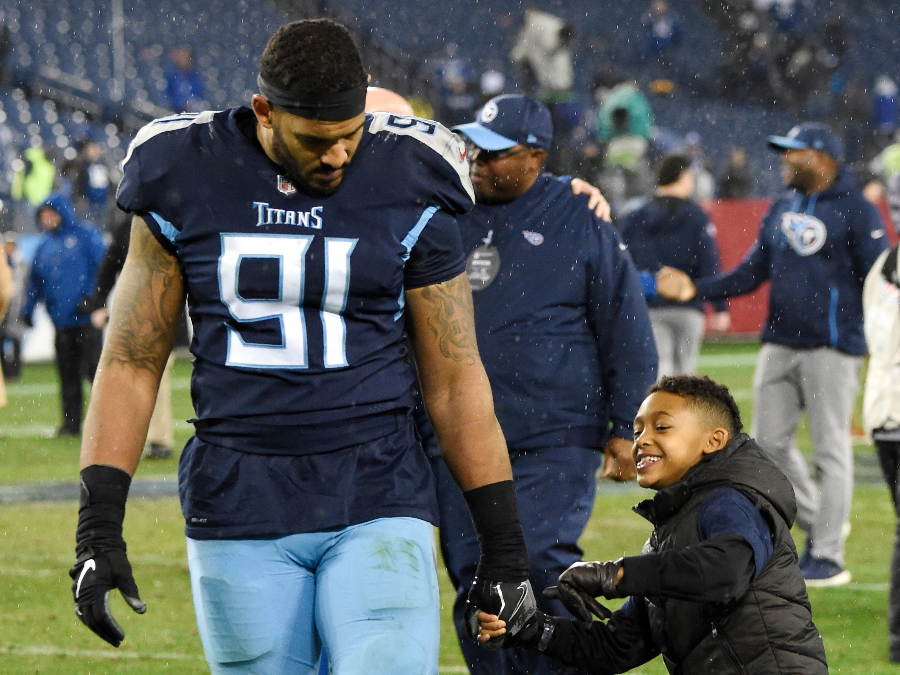 Titans linebacker Derrick Morgan (91) walks off the field with his son Elias after the team's 33-17 loss to the Colts at Nissan Stadium Sunday, Dec. 30, 2018, in Nashville, Tenn.