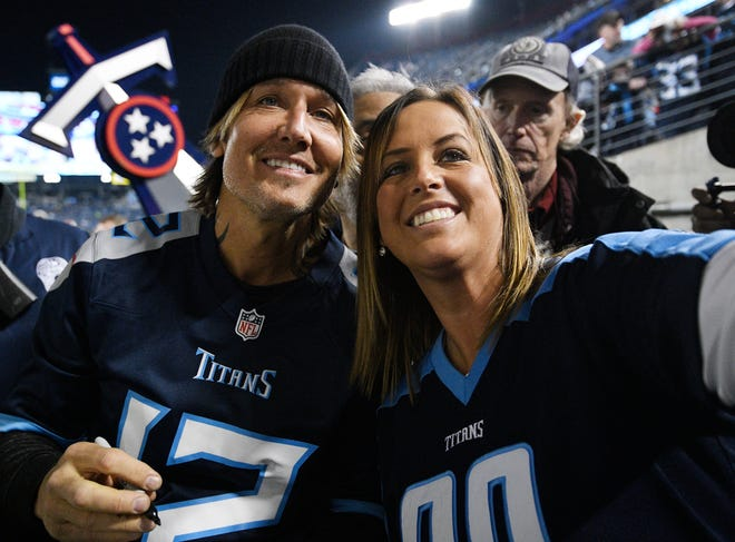 Keith Urban poses for a photo with a fan before the game Sunday at Nissan Stadium.