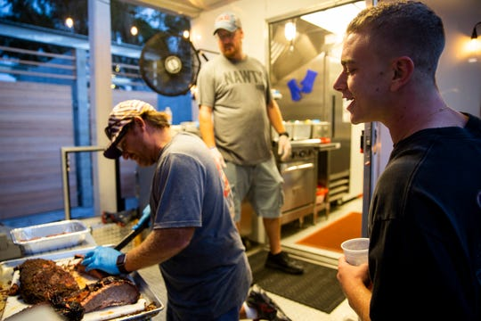 David Mazzarella, right, watches as Aric Tousignant slices a brisket at the Nawty Hogg Backyard BBQ food truck in November 2018, at Celebration Park in Naples. The business plans to open a brick-and-mortar soon in the former Joey D's at Collier Boulevard and Pine Ridge Road.