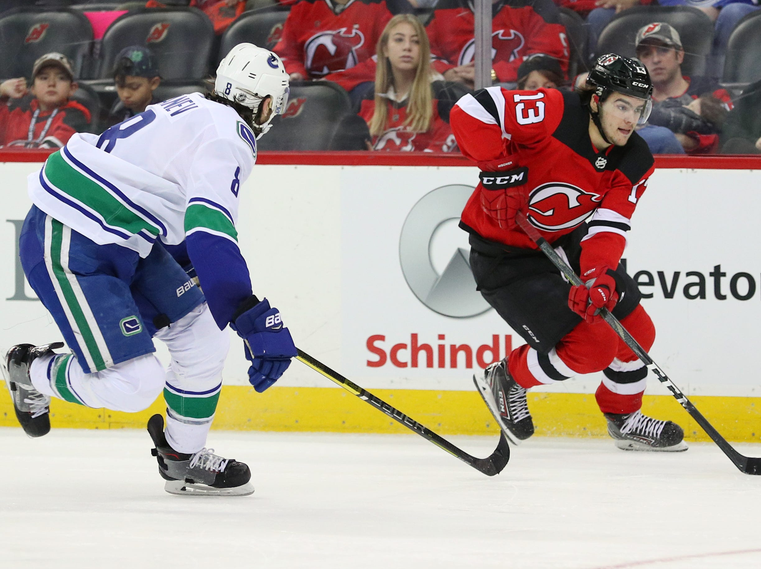 Dec 31, 2018; Newark, NJ, USA; New Jersey Devils center Nico Hischier (13) skates with the puck while being defended by Vancouver Canucks defenseman Christopher Tanev (8) during the second period at Prudential Center.