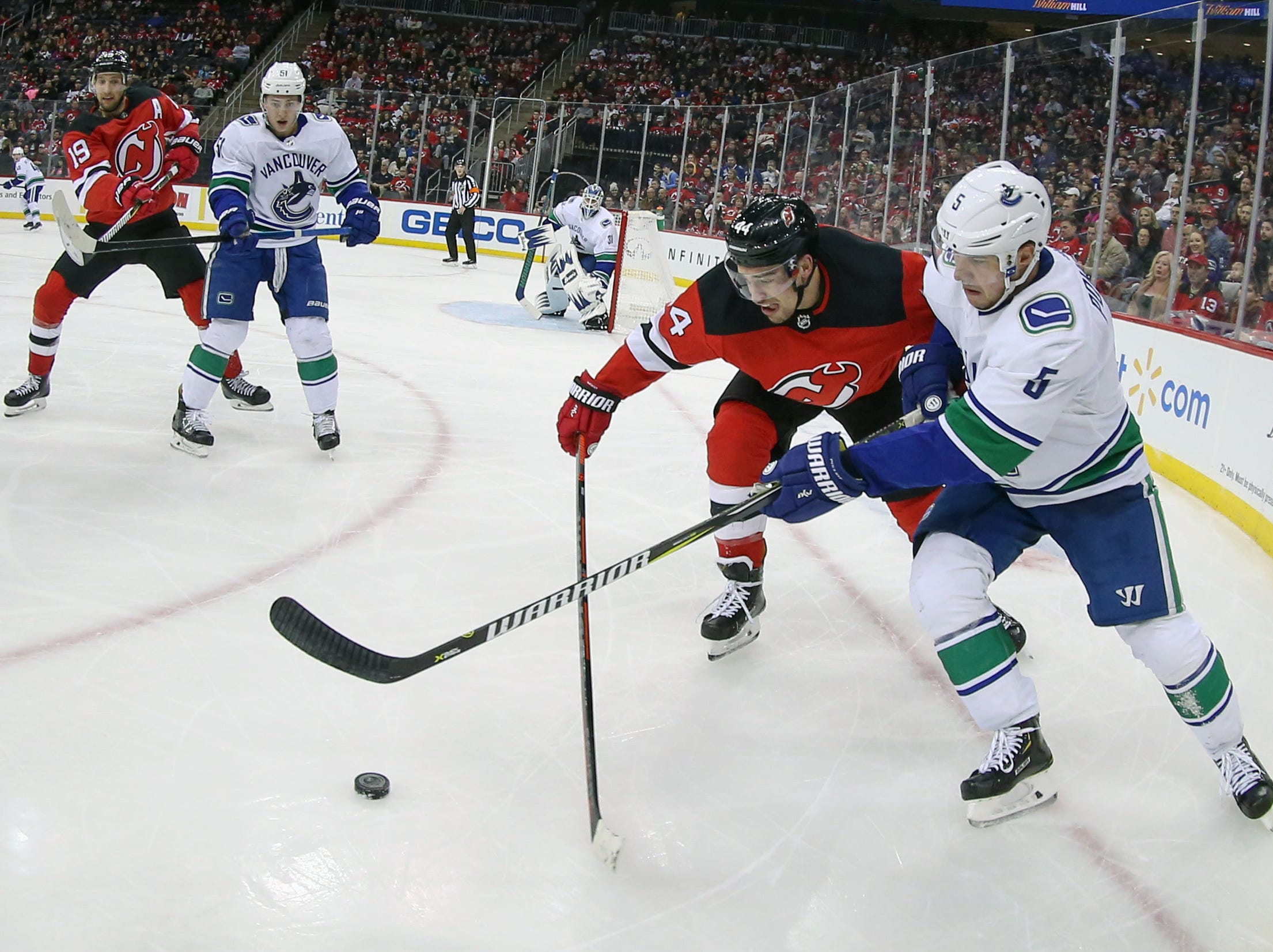 Dec 31, 2018; Newark, NJ, USA; New Jersey Devils left wing Miles Wood (44) battles for the puck against Vancouver Canucks defenseman Derrick Pouliot (5) during the second period at Prudential Center.