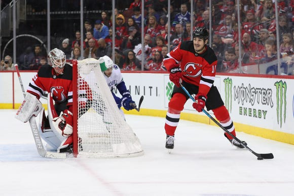 Dec 31, 2018; Newark, NJ, USA; New Jersey Devils center Brian Boyle (11) skates with the puck as goalie Mackenzie Blackwood watches during the first period of their game against the Vancouver Canucks at Prudential Center.