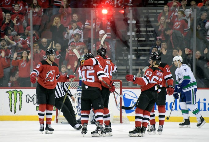 New Jersey Devils left wing Miles Wood (44) celebrates his goal with Drew Stafford (18), Sami Vatanen (45), Jesper Bratt (63) and Nico Hischier (13) during the first period of an NHL hockey game Monday, Dec. 31, 2018, in Newark, N.J.