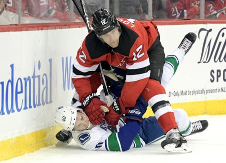New Jersey Devils defenseman Ben Lovejoy (12) checks Vancouver Canucks center Elias Pettersson (40) during the first period of an NHL hockey game Monday, Dec. 31, 2018, in Newark, N.J.