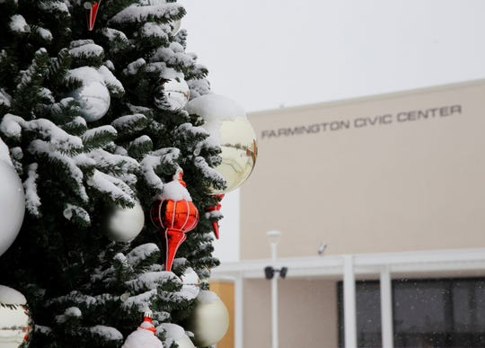 Snow accumulates on the Christmas tree ornaments outside the Farmington Civic Center on Monday.
