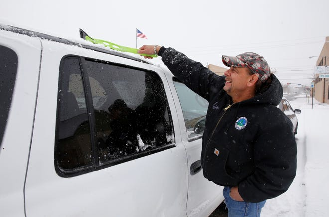 Mike Archuleta removes snow Monday from his vehicle parked on North Behrend Avenue in Farmington.