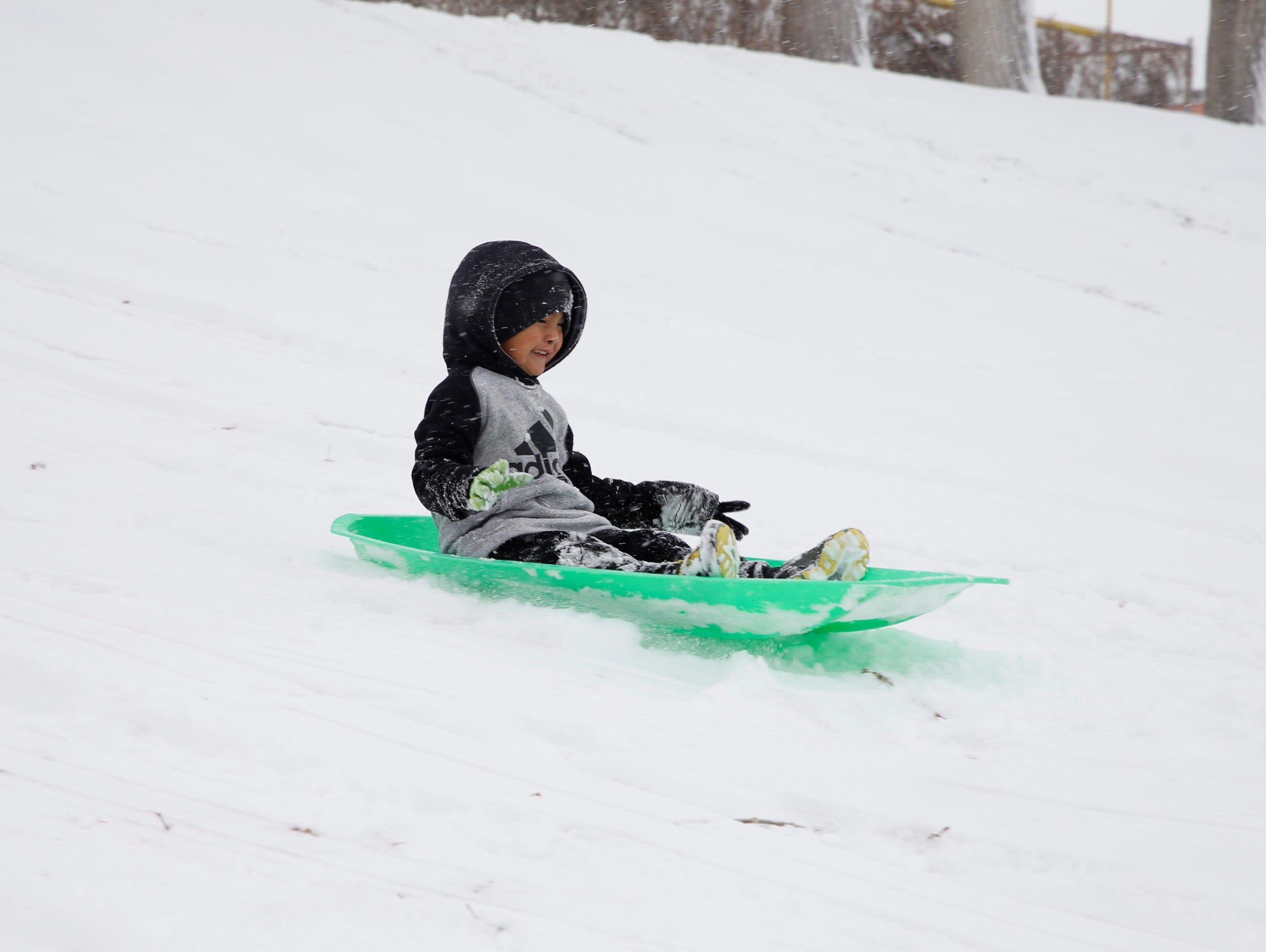 Karnell Jacquez slides down a hill on Monday at Civitan Park in Farmington.
