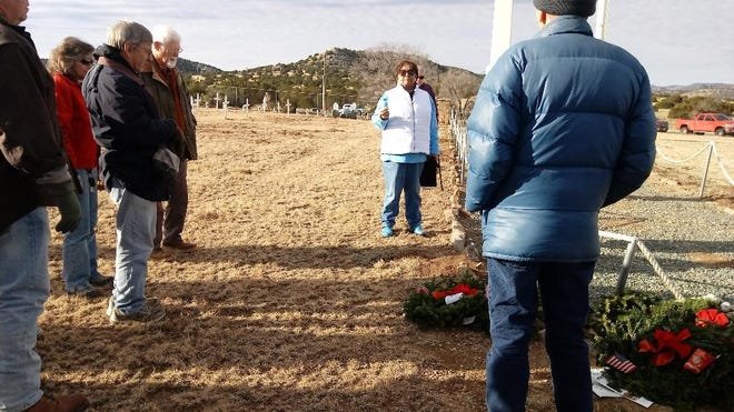 Volunteers gather before placing the wreaths on the graves of veterans at Fort Stanton