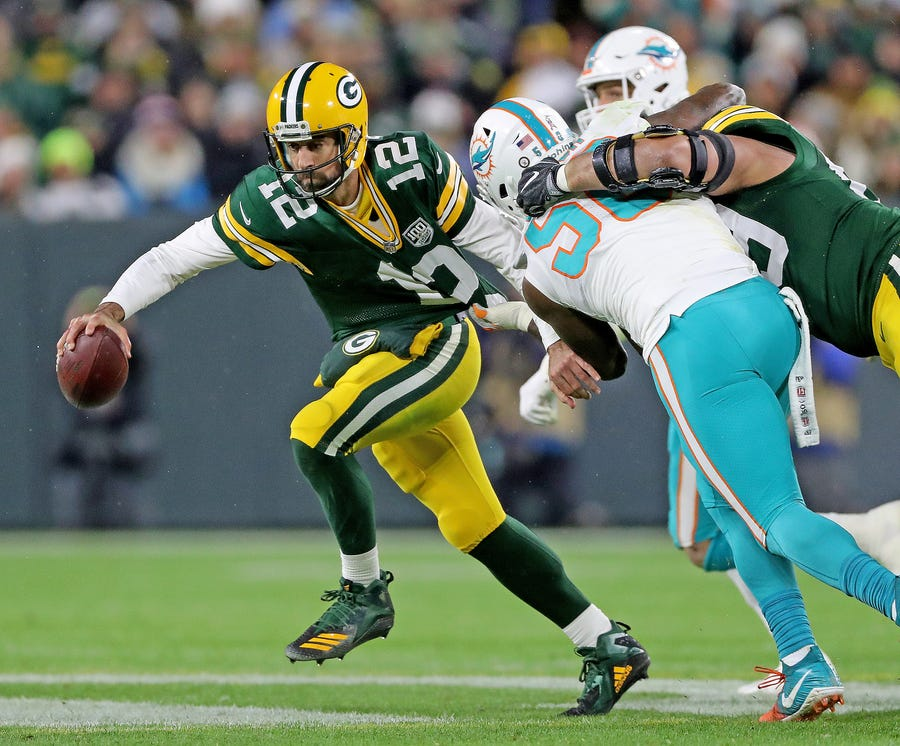 Green Bay Packers quarterback Aaron Rodgers (12) narrowly escapes a sack against the Miami Dolphins at Lambeau Field Sunday, November 11, 2018 in Green Bay, Wis. Jim Matthews/USA TODAY NETWORK-Wis