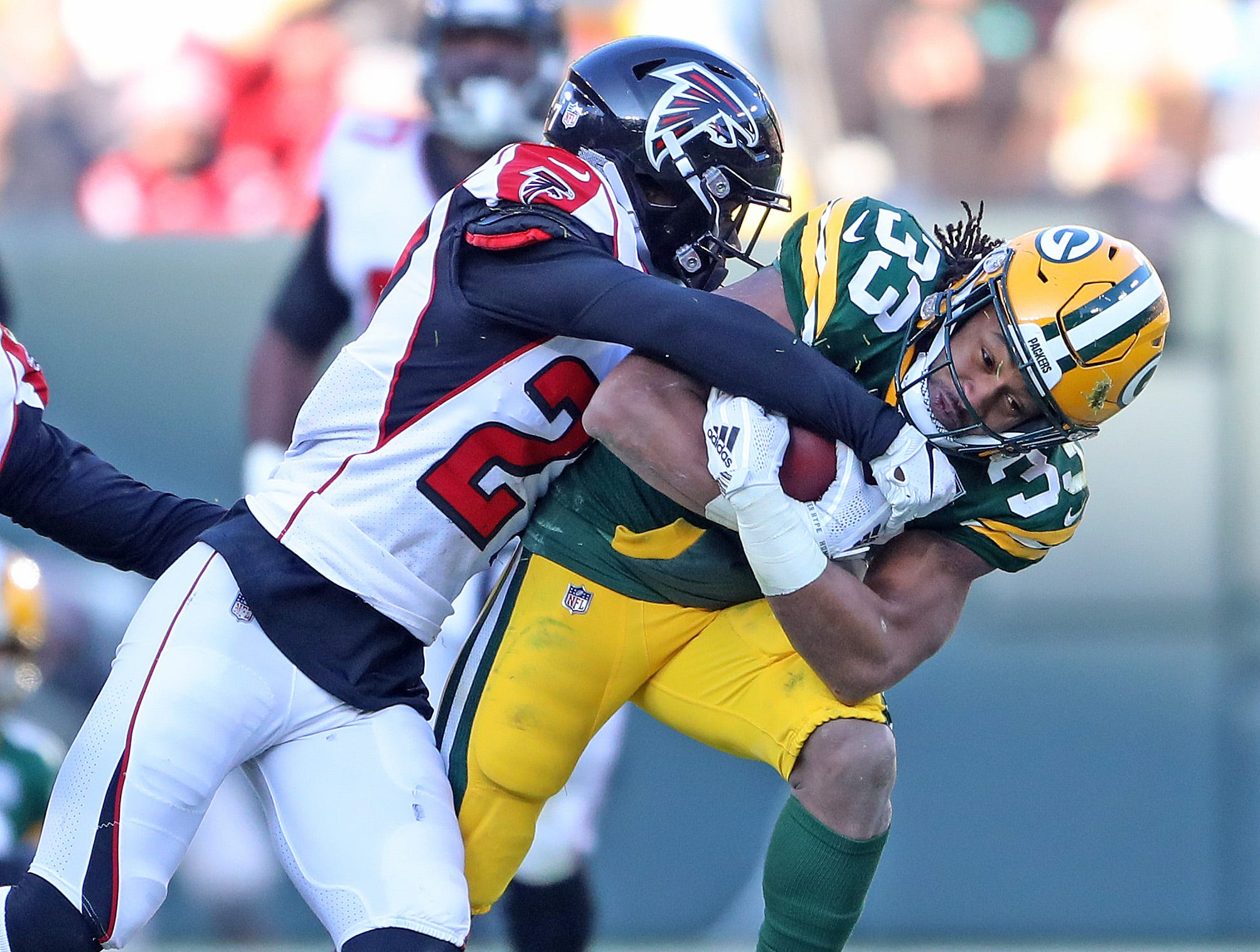 Green Bay Packers running back Aaron Jones (33) takes a hit against the Atlanta Falcons Sunday, December 9, 2018 at Lambeau Field in Green Bay, Wis. Jim Matthews/USA TODAY NETWORK-Wis