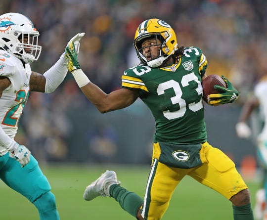 Green Bay Packers running back Aaron Jones (33) fends off a tackler against the Miami Dolphins at Lambeau Field Sunday, Nov. 11, 2018.